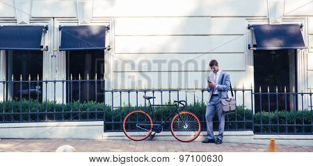 Full length portrait of a happy businessman using smartphone outdoors