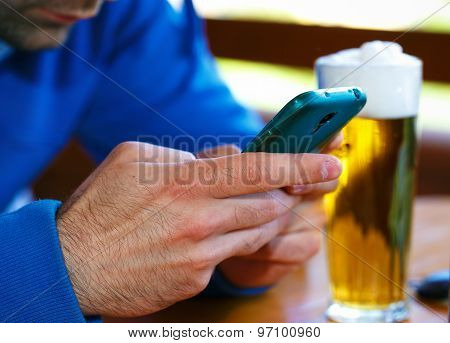 Closeup Of Male Hands With  Smart Phone And  Beer Background