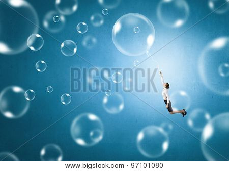 Young businesswoman flying high in sky on soap bubble