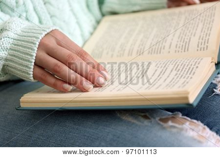 Woman reading book on sofa close up