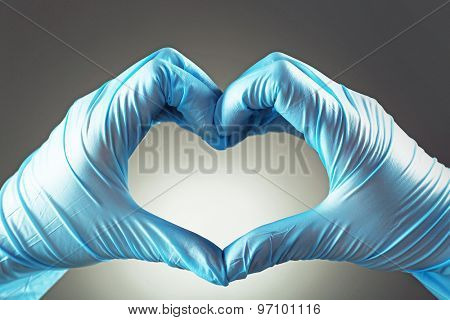 Doctor's hands making heart shape on gray background