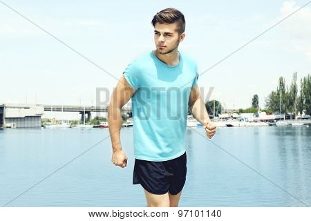 Young man jogging near river