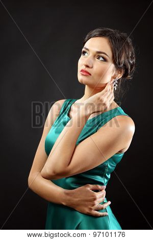 Attractive woman in green dress on dark background