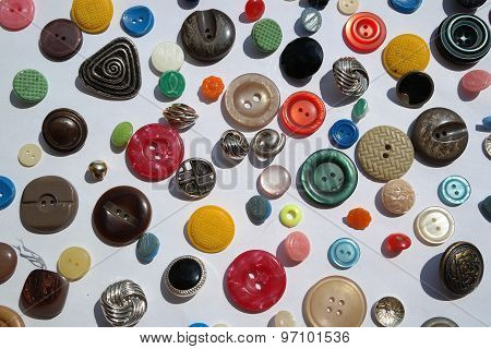 many bright colored variety of round buttons, different textures, diameter, on a white background