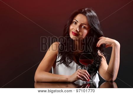 Pretty young woman with wineglass on black background