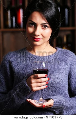 Pretty young woman with wineglass on wine shelf background