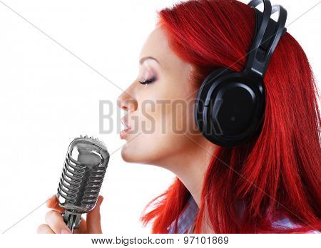 Beautiful young woman singing with microphone isolated on white