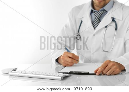 Doctor working at table isolated on white