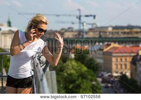 Beautiful young woman talking on mobile phone while standing on the roof.