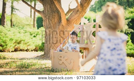 Boy and girl playing in a cardboard boat