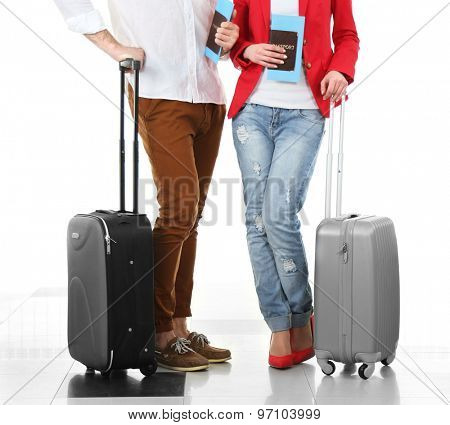 Legs of young happy couple with baggage in airport
