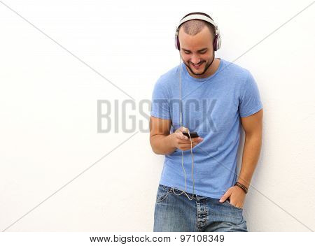 Smiling Man Standing With  Mobile Phone And Headphones