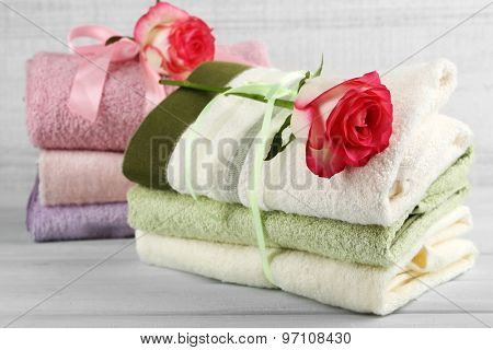 Stack of colorful towels on light wooden background