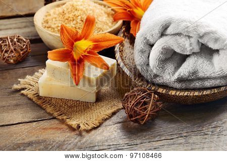 Beautiful spa composition with flowers on wooden table close up