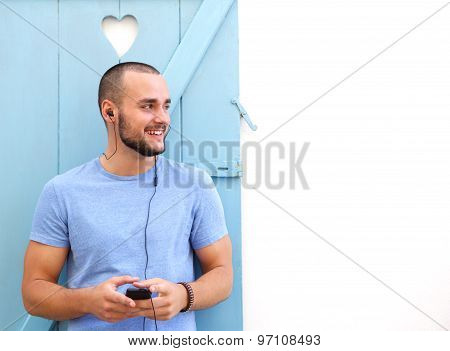 Smiling Man Listening To Music On Mobile Phone With Earphones