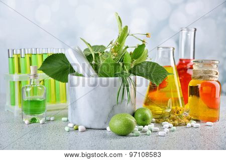 Herbs in mortar, test tubes and pills,  on table, on light background