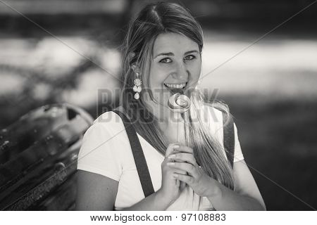 Monochrome Portrait Of Cute Woman Licking Lollipop At Park