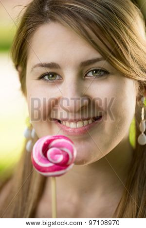 Portrait Of Cute Smiling Woman Holding Big Lollipop
