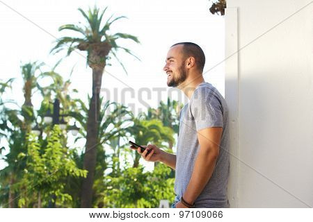 Side Portrait Of A Handsome Young Man Holding Mobile Phone
