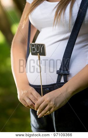 Closeup Of Pregnant Woman Holding Blackboard With Word