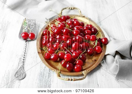 Cherries on tray, on wooden background