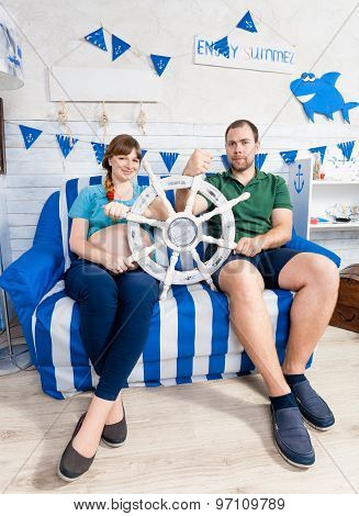Pregnant Wife And Man Posing With Yacht Helm At Living Room