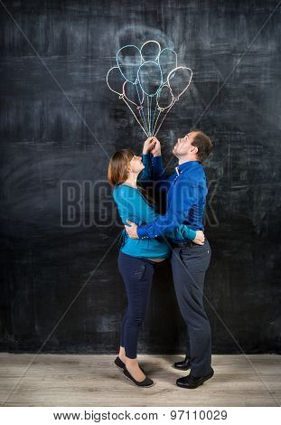 Pregnant Couple Flying Up On The Balloons Drawn On Chalkboard