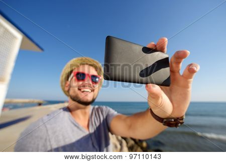 Smiling Young Man On Vacation At The Beach Taking Selfie