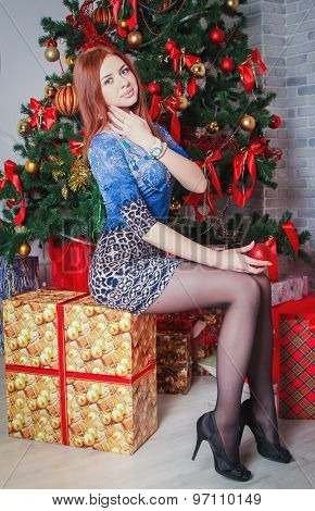 Girl sitting near christmas tree