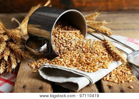 Wheat in metal cup on wooden table, closeup