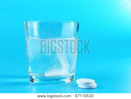 Glass of water and pills on blue background