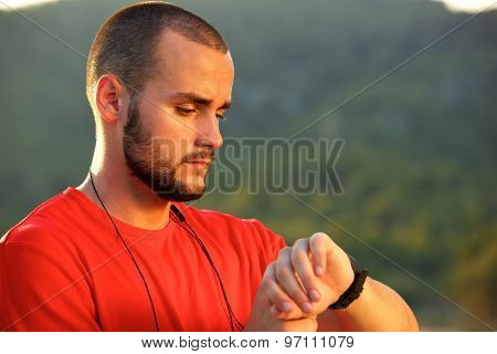 Athletic Man Standing Outside Checking Watch