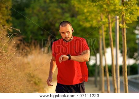 Man Running Outdoors Checking Time On Watch