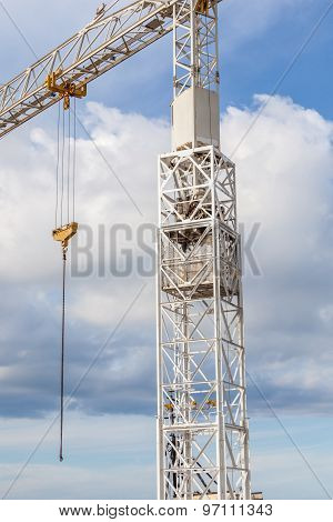 The Big Hoisting Crane Working Contrasts With Cloudy Blue Sky Background.