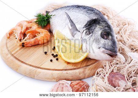Fresh dorado fish and shrimps on wooden cutting board, closeup