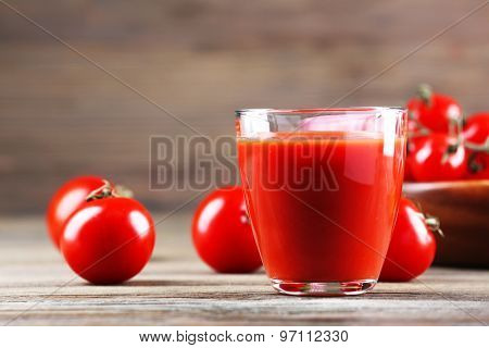 Glass of tomato juice with vegetables on wooden table close up