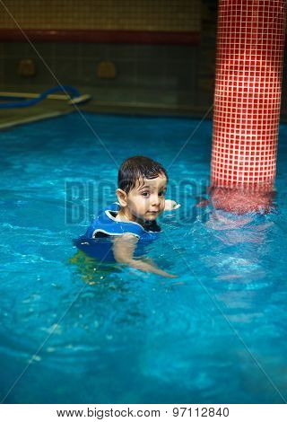 Boy at the Pool with inflatable swimming vest, an indoor swimming pool.