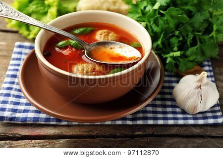 Tomato soup with meat balls on wooden spoon on wooden background