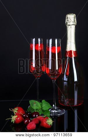 Glasses of champagne with berries on black background
