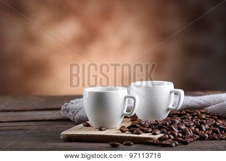 Cups of coffee and beans on blurred background