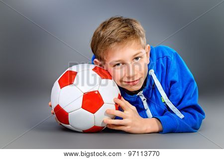 Portrait of a smiling teen boy with football. Studio shot.