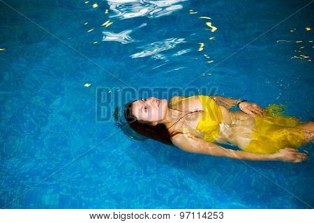 portrait of a young woman relaxing in a swimming pool. swim in the pool and yellow swimsuit.