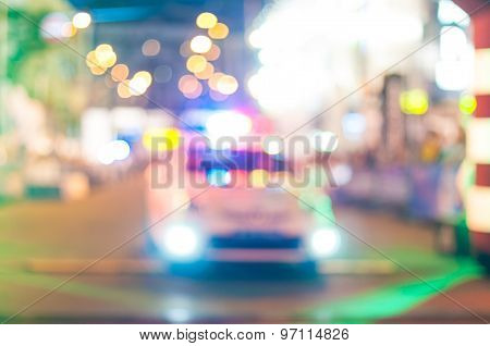 Motion blurred police car with lights turned on at night street