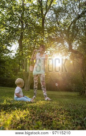 Cheerful Young Mother Blowing Soap Bubbles Towards  Her Baby Boy As He Sits On The Grass