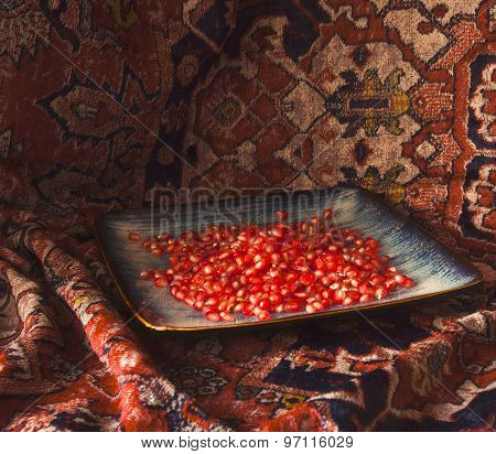 Ripe red Pomegranate seeds on a ceramic dish