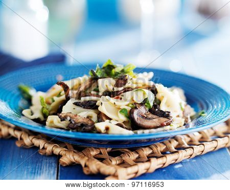farfalle bow tie pasta with mushrooms and chopped basil on blue plate