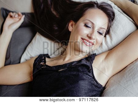 young brunette woman in loft laying on bed smiling seductive
