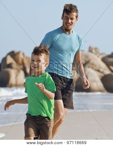 happy family on beach playing, father with son walking sea coast, rocks behind smiling enjoy summer