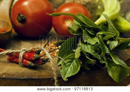 vegetables on wooden kitchen with spicies, tomato, chilli, green