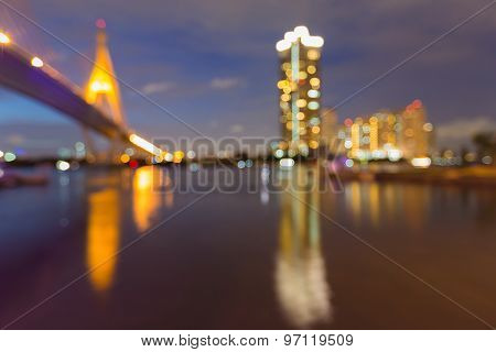 Beauty of city building lights and the bridge with water reflection, abstract blurred bokeh backgrou